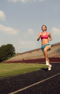 a-healthy-young-woman-running-outdoors-on-a-track-pv